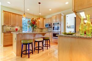 Cozinha com móveis em madeira com Granito na pia e espelhos altos.